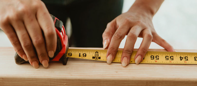 Female carpenter measuring the lumber - Image by © rawpixel